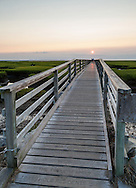 The setting sun glows on the wood of the Bass Hole boardwalk at Gray's Beach, Yarmouth Port.