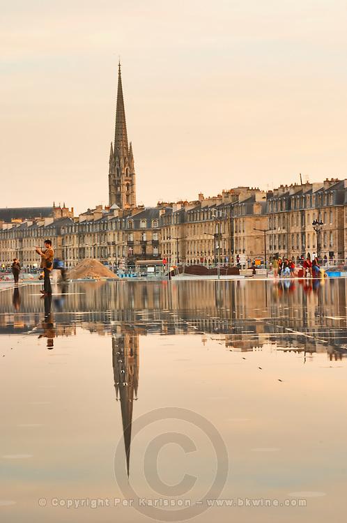 Tower and church Eglise Saint Michel reflected in the fountain. On Les Quais. Place de la Bourse. The new fountain Miroir d'Eau, Water Mirror, making reflections. Bordeaux city, Aquitaine, Gironde, France