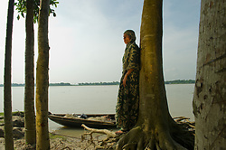 """Mamtaz Begum, 35, stands next to the river and cries in the fishing village of South Tetulbarian in Barguna Sadar upazila  in Bangladesh  October 19, 2010 . Her husband died in a boat accident after capsizing because violent weather. Her mother died later in a cyclone and now she is left with 4 children to feed and very little means to support them. Because of climate change, the seas are getting more violent, less predictable and boats are capsizing more frequently. Twenty percent of the women in this village are widows because so many have lost their husbands in the seas. Coastal and fishing populations are particularly vulnerable and Fishing communities in Bangladesh are subject not only to sea-level rise, but also flooding and increased typhoons. Erosion as a result of stronger and higher tides, cyclones and storm surges is eating away Bangladesh's southern coast.  Yet the largely fishing community cannot live without the sea. """"We only know how to catch fish,"""" say the fishermen. ( Ami Vitale)"""
