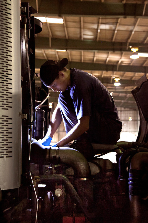 Mechanic sitting on top of waste collection truck engine fixing it