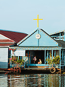 A young boy and girl wait in the entrance way to a Christian church in one of the floating village communities of the great Tonlé Sap lake, Cambodia