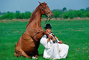 Hugarian Csikos - Cowboy - with his horse resting his hoof on his leg  at Bugac on the Great Plain of Hungary