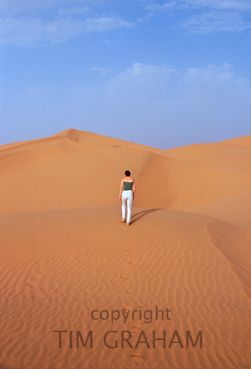 Tourist climbing up a sand dune in the Sahara Desert, Morocco