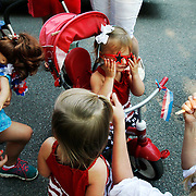 Addison Hewett, 2, center, adjusts her star sunglasses with the help of her mom Anna Pepper Hewett, bottom right, before walking down Calhoun Street for The Bluffton Children's Fourth of July Parade on July 4, 2014.