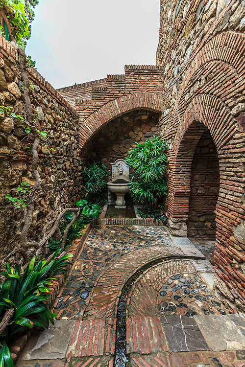 Water rill and Fuente de la Ballena in the Alcazaba of Málaga in Malaga, Spain. Water rills are used to flood beds or water trees in orchards.  They still act as canals to bring water into garden area for irrigation.