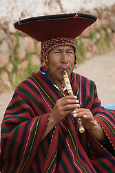 Flute seller playing flute in market, Chinchero (near Cuzco), Peru, South America