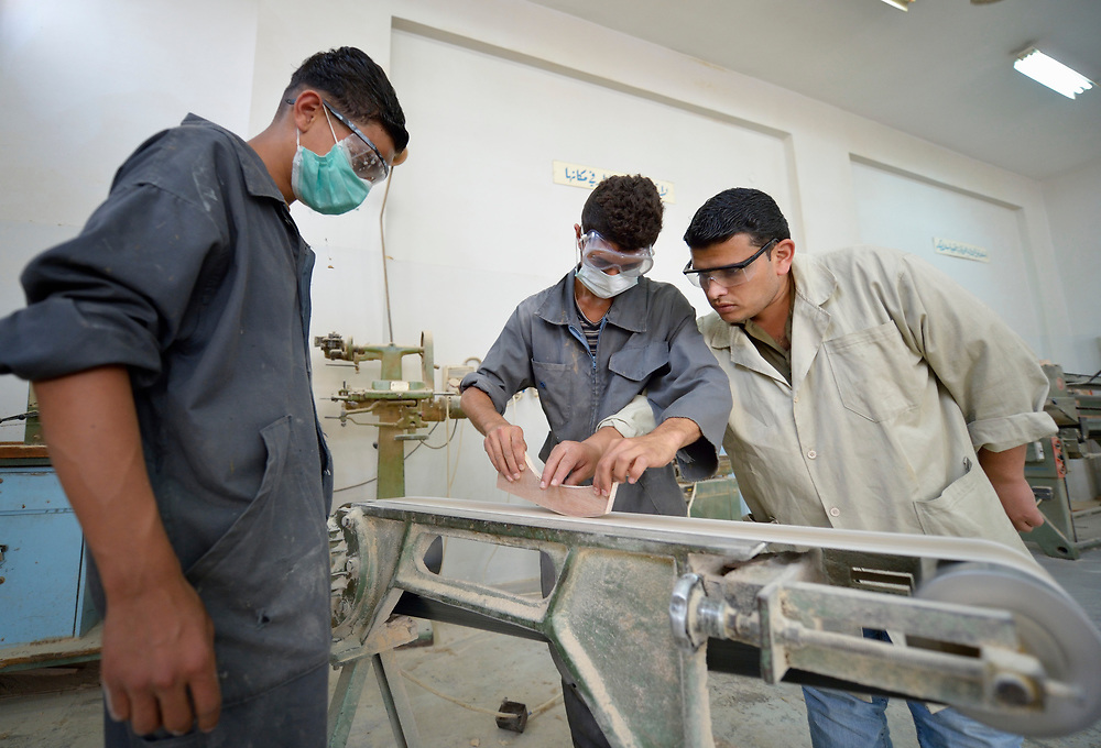 Instructor Ishamis Abu Mhasin helps students learn to use a belt sander in a woodworking class in the Vocational Training Center in Gaza City, Gaza. The center is run by the Department of Service for Palestinian Refugees of the Near East Council of Churches, a member of the ACT Alliance, and funded in part by the Pontifical Mission for Palestine.