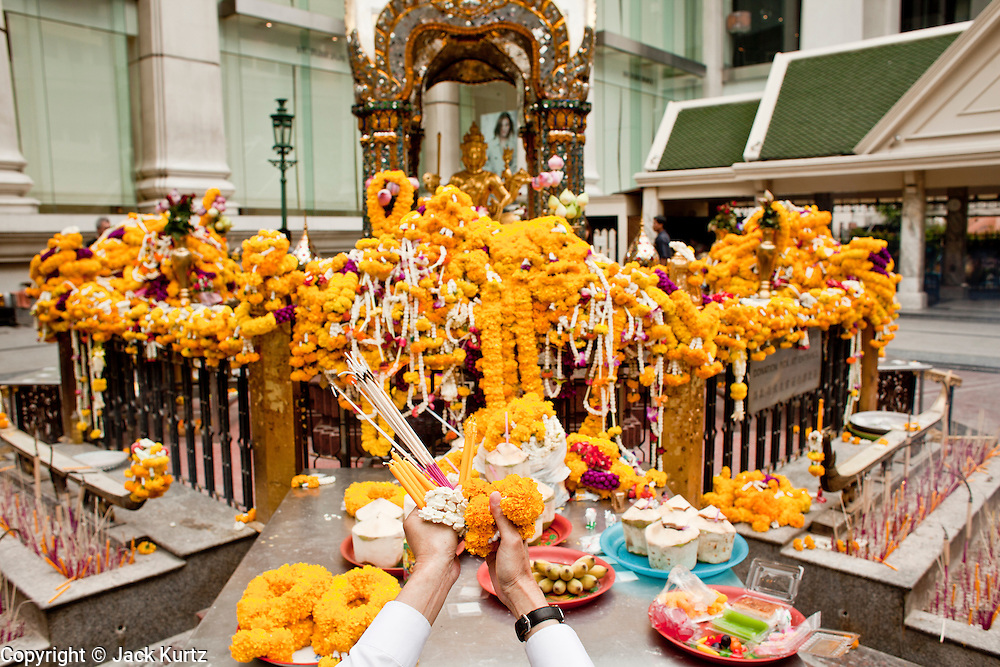 26 MARCH 2010 - BANGKOK, THAILAND: A man offers flower garlands and incense to the Erawan Shrine in Bangkok. The Erawan Shrine (Thai: San Phra Phrom) is a Hindu shrine in Bangkok, Thailand that houses a statue of Phra Phrom, the Thai representation of the Hindu creation god Brahma. The Erawan Shrine was built in 1956 as part of the government-owned Erawan Hotel to eliminate the bad karma believed caused by laying the foundations on the wrong date. The hotel's construction was delayed by a series of mishaps, including cost overruns, injuries to laborers, and the loss of a shipload of Italian marble intended for the building. Furthermore, the Ratchaprasong Intersection had once been used to put criminals on public display. An astrologer advised building the shrine to counter the negative influences. The Brahma statue was designed and built by the Department of Fine Arts and enshrined on 9 November 1956. The hotel's construction thereafter proceeded without further incident.      PHOTO BY JACK KURTZ