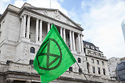 An Extinction Rebellion flag is pictured in front of the Bank of England before the Blood Money March through the City of London on the fifth day of Impossible Rebellion protests on 27th August 2021 in London, United Kingdom. Extinction Rebellion were intending to highlight financial institutions funding fossil fuel projects, especially in the Global South, as well as law firms and institutions which facilitate them, whilst calling on the UK government to cease all new fossil fuel investment with immediate effect.