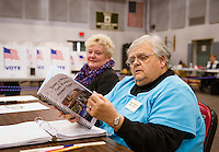 Gail Garfield and Sharon Wright looking over the Belmont Annual Report as they wait for voters to check in on Tuesday morning at Belmont High School.  (Karen Bobotas/for the Laconia Daily Sun)