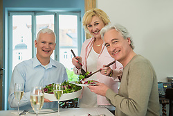 Woman serving salad to her friends, smiling