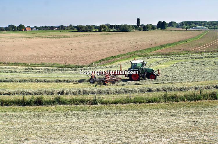 Nederland, Ooijpolder, 25-5-2020 In de uiterwaarden van de rivier de Waal is een boer bezig met gras binnenhalen. Daarna wordt het tot balen hooi verpakt en als wintervoer aan het vee, de koeien, gevoerd. Door de aanhoudende droogte groeit het gras minder hard waardoor er minder binnengehaald kan worden . Op de achtergrond zijn watersproeiers bezig land te beregenen . Foto: Flip Franssen