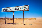 Tropic of Capricorn road sign plastered with tourist stickers in the Namib Desert, Namibia, Africa