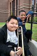 Black and Asian teen musicians from Ramsey school resting after performance. Grand Old Day Festival. St Paul Minnesota MN USA