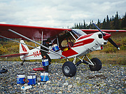 Hollis Twitchell loading five gallon gas cans in teh back of Lake Clark National Park's Super Cub, trash cleaned from gravel bar strip on the Mulchatna River, Alaska.