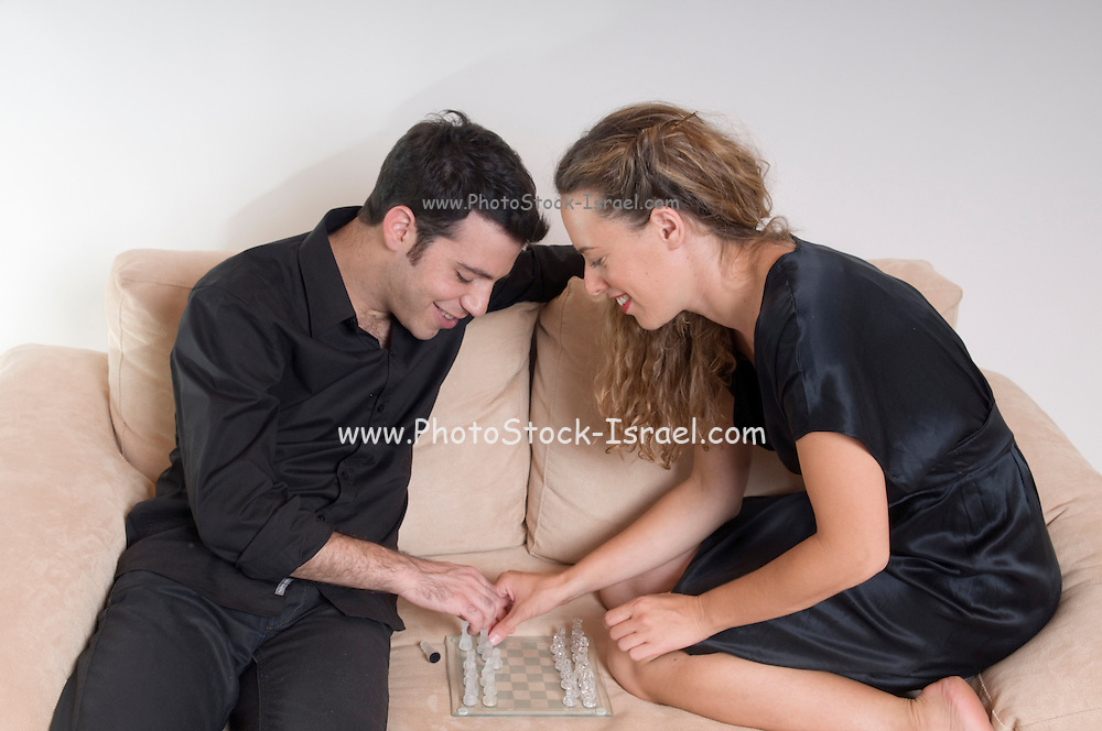 A young couple in their 20s sharing an intimate moment playing chess on a sofa on a white background Model Releases available