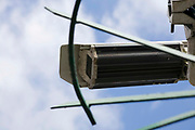 CCTV camera fixed to a building and back lit against a blue cloudy sky. This Closed-Circuit Television (CCTV) camera can record images for surveillance, which may be relayed to screens in a central control room. They monitor and record activities in all environments. They can be used as deterrents in crime or to identify persons involved in illegal activities.