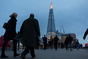 Evening rush-hour commuters walk across London Bridge towards the Shard on the southbank, on 9th November 2018, in London England.