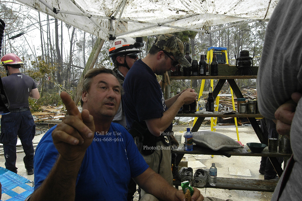 Brian Mollerie speaks to federal search and rescue team in wavelan ms. Mr. Mollerie rode out the storm in his home with his dog, salvaged a tent after the storm and is now camped out on the slab that used to be his home. The wave of water that hit waveland is estimated to have been 30 feet high.he found during a search and rescue mission in Waveland,Mississippi Tuesday August 31,2005. Wavelan was in Hancock county and was one of the hardest hit communities.(photo/Suzi Altman)