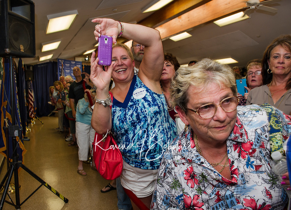 Karen Lewandowski is ready as Republican Presidential candidate Donald Trump is introduced to the packed house at the Weirs Beach Community Center on Thursday evening.  (Karen Bobotas/for the Laconia Daily Sun)