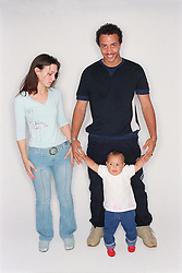 Young mother and father standing together with baby daughter,