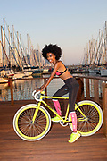 Young female African cyclist resting after an outdoor workout. The yachts in the Tel Aviv Marina the background