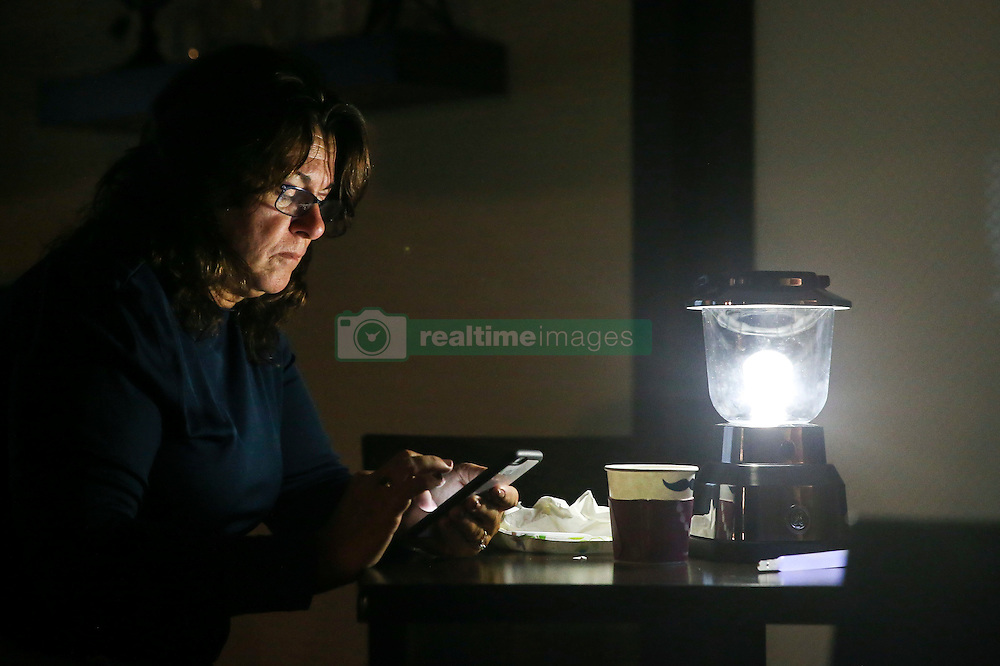 October 7, 2016 - Titusville, Florida, U.S. - WILL VRAGOVIC       Times.Margaret Bodchon, 56, of Merritt Island, checks text messages and weather updates as she drinks coffee by lantern light in the lobby of the Hampton Inn while Hurricane Matthew rages outside in Titusville, Fla. on Friday, Oct. 7, 2016. ''As each hour passes, it looks better and better than it did yesterday,'' she said. The storm took a northeasterly turn overnight that seems to have spared Florida a direct hit. (Credit Image: © Will Vragovic/Tampa Bay Times via ZUMA Wire)