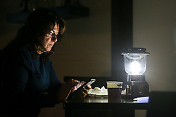 October 7, 2016 - Titusville, Florida, U.S. - WILL VRAGOVIC   |   Times.Margaret Bodchon, 56, of Merritt Island, checks text messages and weather updates as she drinks coffee by lantern light in the lobby of the Hampton Inn while Hurricane Matthew rages outside in Titusville, Fla. on Friday, Oct. 7, 2016. ''As each hour passes, it looks better and better than it did yesterday,'' she said. The storm took a northeasterly turn overnight that seems to have spared Florida a direct hit. (Credit Image: © Will Vragovic/Tampa Bay Times via ZUMA Wire)