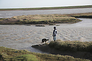 Boy and dog on salt marsh, Shingle Street Orford Ness spit, Suffolk, England