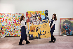 © Licensed to London News Pictures. 01/02/2012. LONDON, UK. Sotherby's employees pose with artist Jean-Michel Basquiat's artwork 'Orange Sports Figure' between artworks by Takashi Murakami 'Open Your Hands Wide, Embrace Happiness!' (L) and Cindy Sherman 'Untitled #421' At Sotherby's auction House in London. The Basquit piece is expected to ralise up to £4,000,000 on February 15th 2012. Photo credit: Matt Cetti-Roberts/LNP