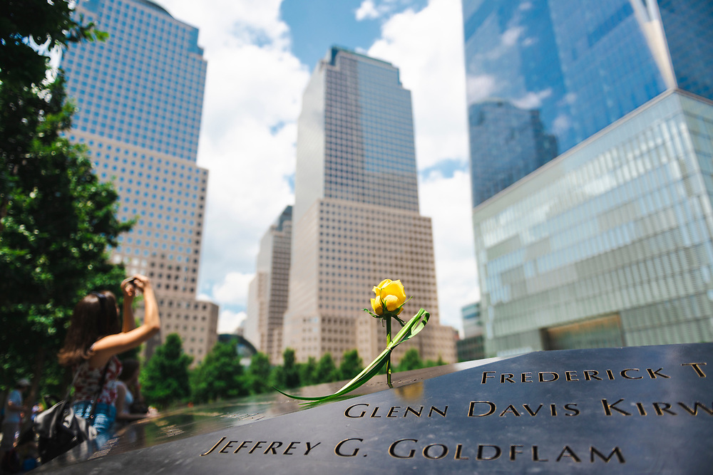 New York City, USA - July 6, 2016: A yellow rose is left at the National September 11 Memorial at Ground Zero in Lower Manhattan. Rising behind it is One World Trade Center (also known as the Freedom Tower), built after the 9/11 attacks.