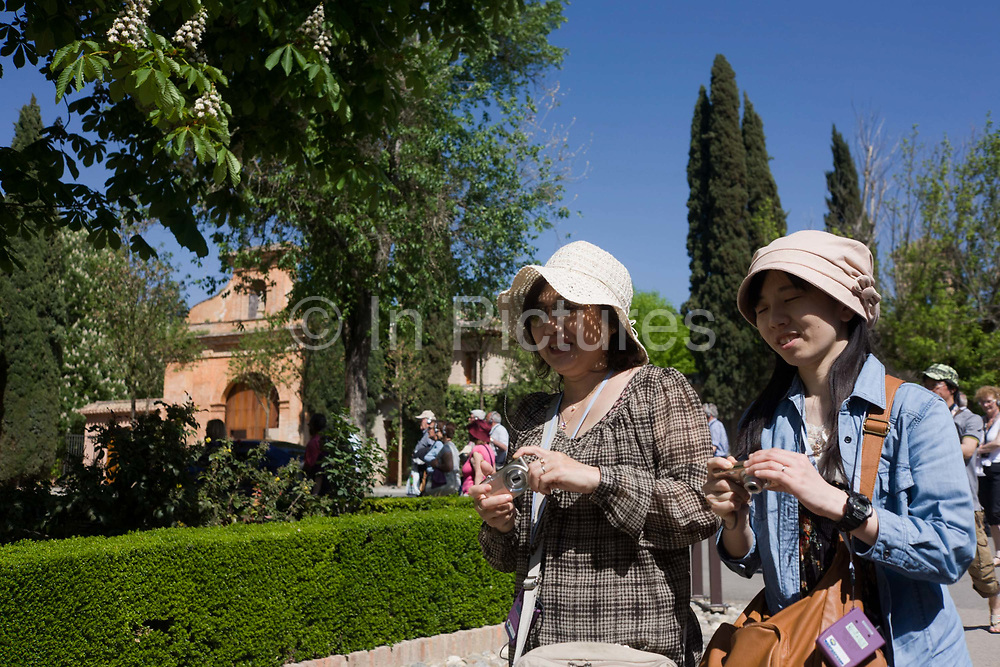Two women tourists from Asia walk in the sunshine at Alhambra, both holding cameras. Both wearing sun hats and holding in the same manner, their compact digital cameras with which to record their European holiday memories. Alhambra (in Arabic, Al-Ḥamra) is a palace and fortress complex constructed during the mid 14th century by the Moorish rulers of the Emirate of Granada in Al-Andalus.