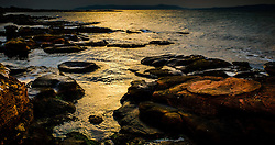 Evening light on the rocks at Skate Bay on the west coast of the island of Great Cumbrae, Scotland.  The Isle of Bute can be seen in the background.<br /> <br /> (c) Andrew Wilson   Edinburgh Elite media