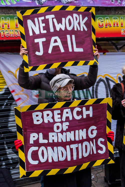 February 4, 2018 - London, UK. 4th February 2018. Artist Andrew Cooper points out his sculpture of theheads of Lambeth Councillors responsible for social cleansing to Aysen Dennis from the Aylesbury Estate. Campaigners mark the third anniversary of the announcement by Network Rail of their plans to redevelop the Brixton Arches with a rally and a three minute silence. The  area and its small traders who have been displaced (a few are still fighting to remain) has been described as the 'heart of Brixton'. The work was supposed to be completed by 2016 but is only scheduled to start tomorrow, and the Save Brixton Arches campaign are calling for it to be abandoned as the plans for the work fail to include proper fire safety precautions and will severely restrict access by emergency services to local businesses and the railway and station. They also call on Lambeth Council to insist that the conditions of the planning permission that included no adverse effect on the market traders in Brixton Station Road be applied, as the work as planned will produce dust and pollution which will almost certainly force those who prepare food in the area out of business. They also point out that there are no safety measures to protect local businesses, young children in the nearby crèche or the general public from potentially dangerous airborne particles during the removal of asbestos. There was also a call for an investigation into local Labour MP Helen Hayes, elected in 2015, who until she resigned shortly before the election was a senior partner in the firm Allies & Morrison which made the recommendation for the 'improvement' of the arches in 2013, though she has denied any personal involvement. A&M have been involved in many contentious 'regeneration' schemes with developers and councils across London which opponents describe as social cleansing.  Peter Marshall ImagesLive (Credit Image: © Peter Marshall/ImagesLive via ZUMA Wire)