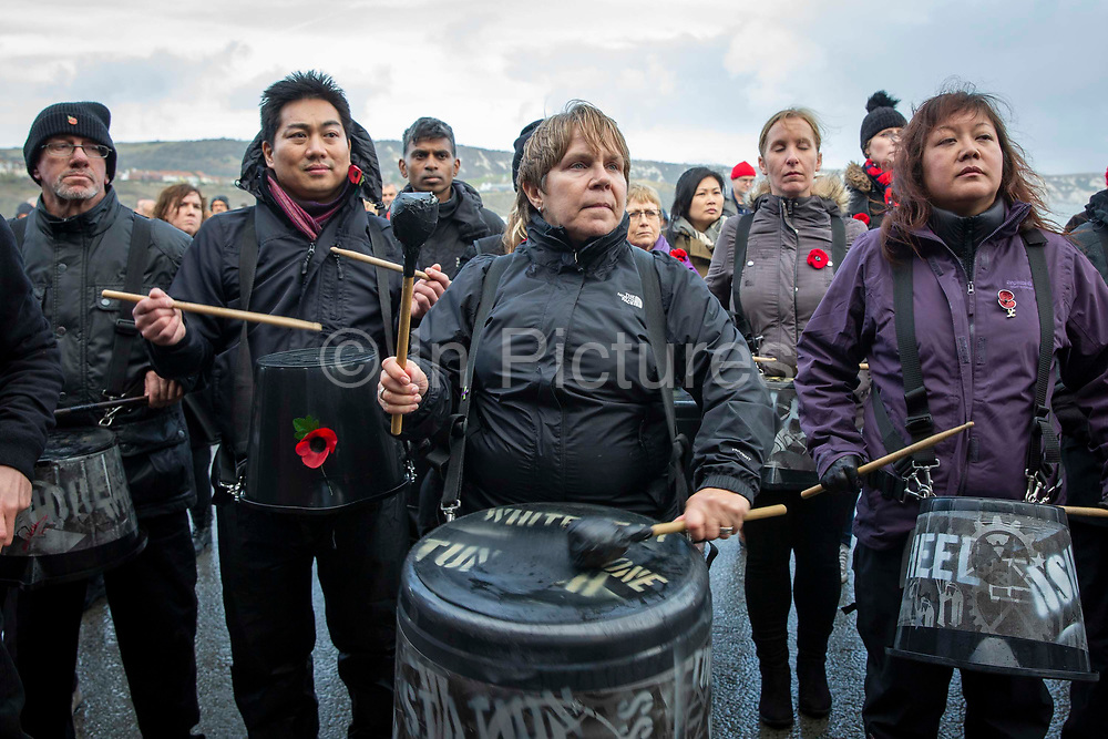 The Pandemonium Drummersfrom the London 2012 Olympic Ceremonies perform Symphony of Waves created forthe Armistice Day centenary remembrance event 'Pages of the Sea'onFolkestone Harbour Arm, Folkestone Kent. 11th November 2018. Presented by over 40 drummers, the semi-improvised piece explores the concern, anxiety, and commitment of those who left home and started a journey across the sea to fight in World War One, from which many did not return. Performed on buckets and bins is is designed to evoke memories of a pleasant land left behind and outlooks of an uncertain future.