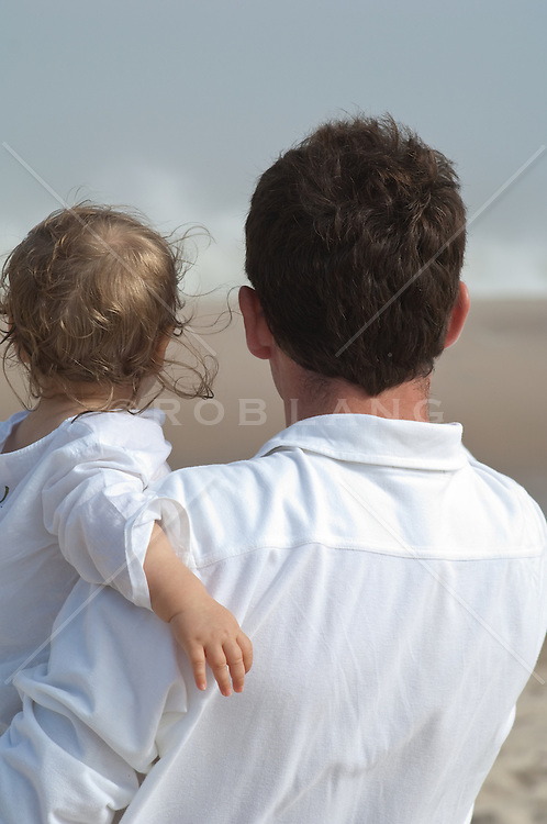 Father holding his child, both looking away from camera