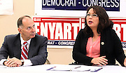U.S. Congressman Bill Enyart listens to Congresswoman Tammy Duckworth speak at his campaign office in downtown Belleville on Thursday morning. The press conference had originally been scheduled to be held at the Scott AFB Heritage Air Park, but inclement weather forced them to move to an inside location. The two spoke primarily about veterans affairs.