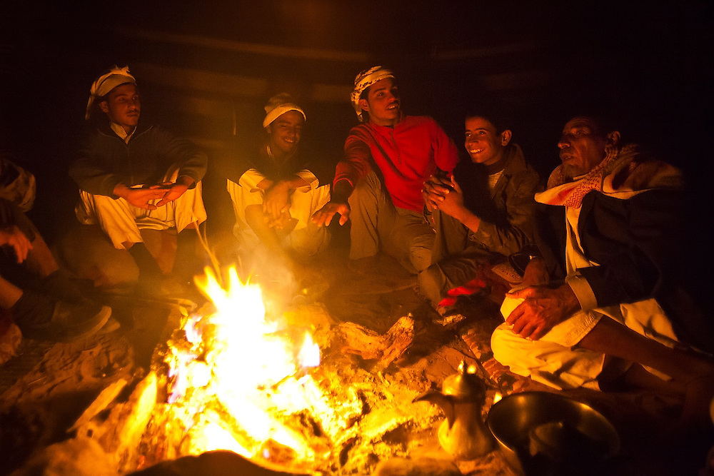 Young Bedouin men and boys relax by a fire listening to their father tell stories in his remote home encampment in Wadi Rum, Jordan.