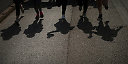 """Shadow of 5 girl carrying the baton as they run on the 20th Korrika.  Hendaia (Basque Country). April 4, 2017. The """"Korrika"""" is a relay course, with a wooden baton that passes from hand to hand without interruption, organised every two years in a bid to promote the basque language. The Korrika runs over 11 days and 10 nights, crossing many Basque villages and cities. This year was the 20th edition and run more than 2500 Kilometres. Some people consider it an honour to carry the baton with the symbol of the Basques, """"buying"""" kilometres to support Basque language teaching. (Gari Garaialde / Bostok Photo)"""