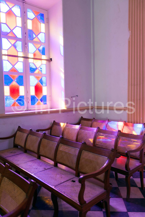 Stained glass and pews in the interior of Notre Dame des Anges church, Pondicherry, India. Built in the 1850s the church is in the  French Quarter of the town and looks out towards the Indian Ocean.