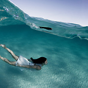 A woman in a white dress swims beneath the ocean's surface over sand.