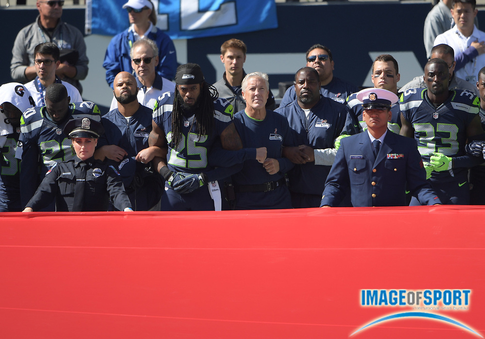 Sep 11, 2016; Seattle, WA, USA; Seattle Seahawks head coach Pete Carroll and cornerback Richard Sherman (25) interlock elbows with players and coaches during the playing of the national anthem during a NFL game against the Miami Dolphins at CenturyLink Field.