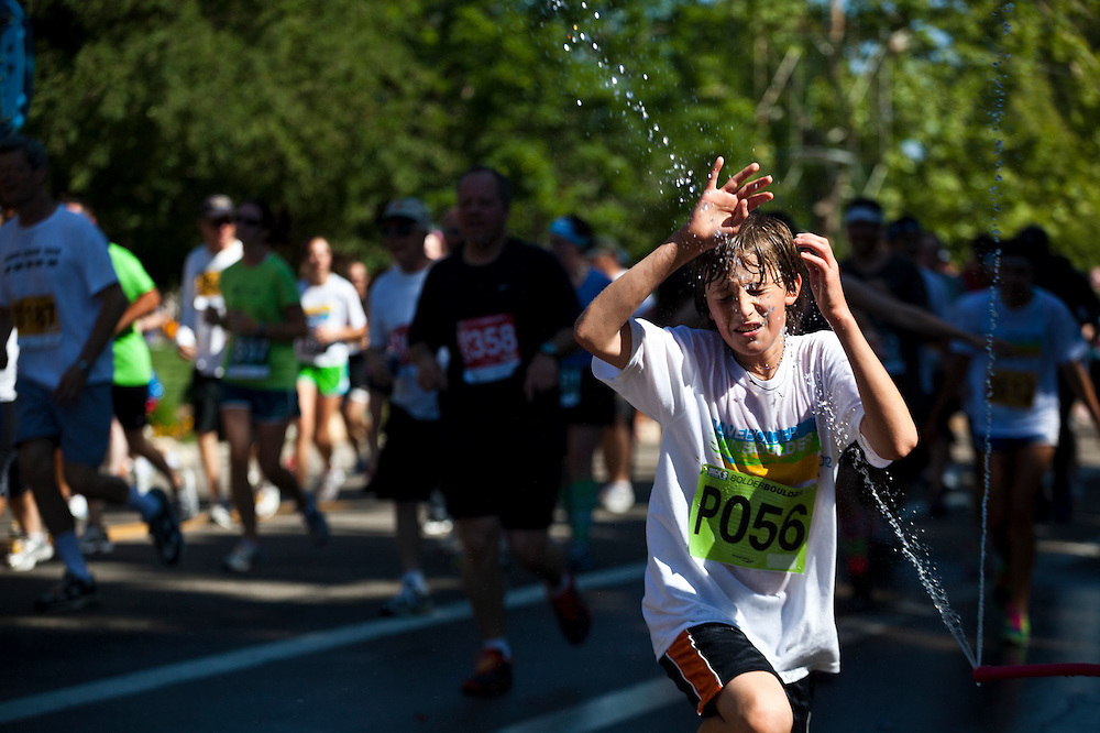 Alessandro Lauria, 12, rushes through a jet of water running in the 2012 Bolder Boulder 10K road race in Boulder, Colorado.