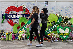 © Licensed to London News Pictures. 14/06/2018. London, UK. Members of the public pay their respects at a memorial at the foot of Grenfell Tower on the first anniversary of the Grenfell Tower Fire in which 72 people were killed. Grenfell Tower caught fire on the night of June 14, 2017 after a small blaze started in one of the flats which spread rapidly up the outside of the 24-floor tower block. A public inquiry is currently underway. Photo credit: Rob Pinney/LNP
