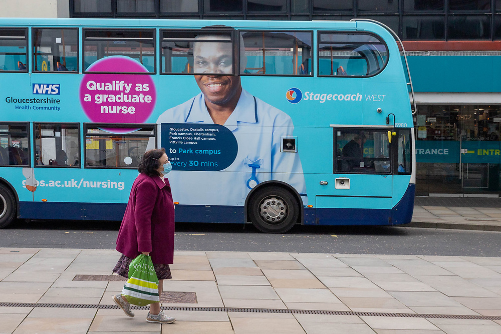 25th February 2021. A woman wearing face mask walks past new NHS and University of Gloucestershire recruitment advertisement