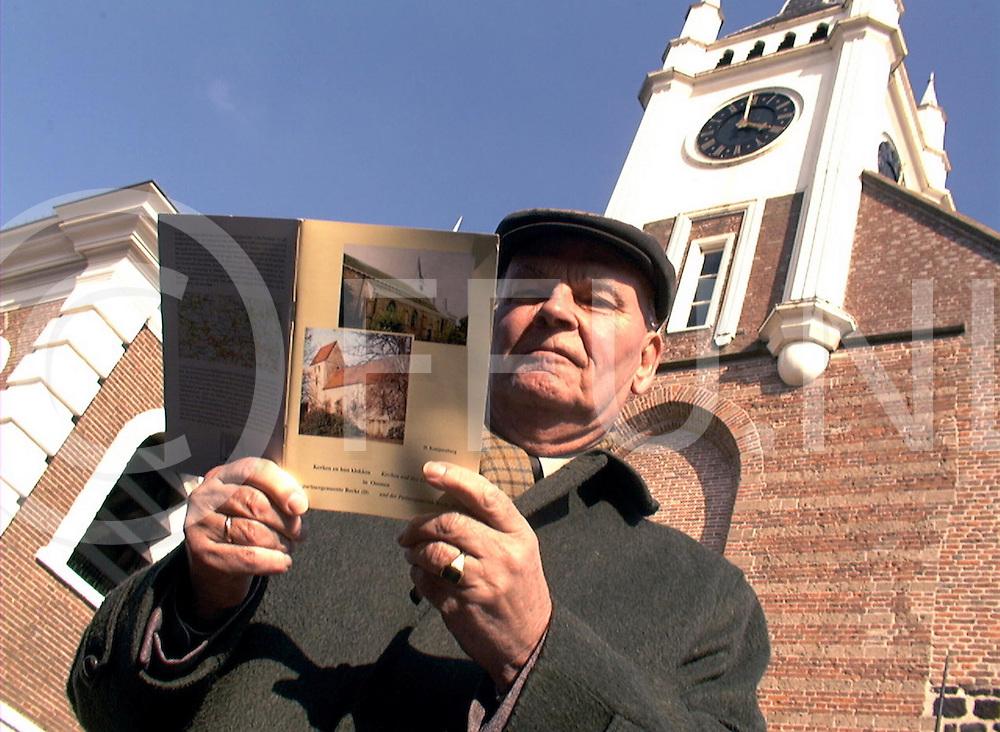 fotografie frank uijlenbroek©2001 michiel van de velde.010327 ommen ned.fu010327_06.ommer nieuws dhr konijnenberg voor de hervormde kerk .met een door hem geschreven boek over ommen