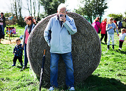 © Licensed to London News Pictures.26/08/15<br /> Egton, UK. <br /> <br /> A man leans against a hay bale with a cup of tea at the 126th Egton Show in North Yorkshire. <br /> <br /> Egton is one of the largest village shows in the country and is run by a band of voluntary helpers. <br /> <br /> This year the event featured wrought iron and farrier displays, a farmers market, plus horse, cattle, sheep, goat, ferret, fur and feather classes. There was also bee keeping, produce and handicrafts on display.<br /> <br /> Photo credit : Ian Forsyth/LNP