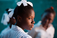 Students welcome a delegation as they study in  a classroom that lost its roof and a wall in the January 12 earthquake, at the Saint Gerard School in Port-au-Prince, Haiti.