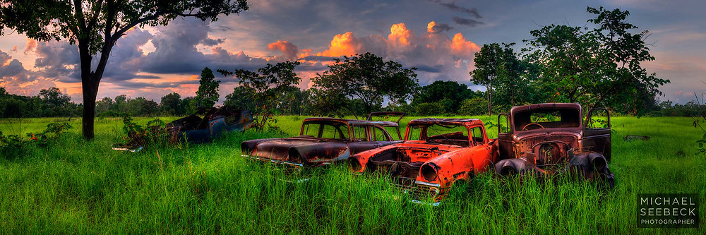 A panoramic photograph of old vintage car wrecks in a field in a rural area near Darwin.<br /> <br /> Code: HATD0003<br /> <br /> Limited Edition of 125