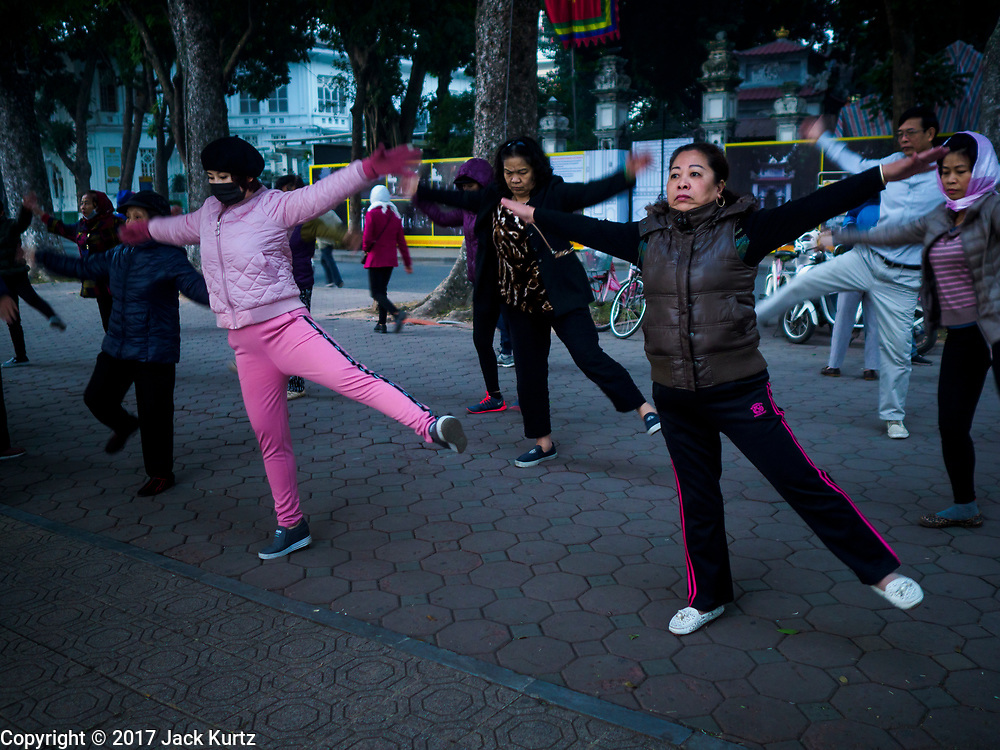 26 DECEMBER 2017 - HANOI, VIETNAM: People workout in an exercise session at Hoan Kiem Lake, in the Old Quarter of Hanoi. Thousands of Vietnamese people line the lake front in the early hours of the morning to perform tai chi and other low impact aerobic workouts.     PHOTO BY JACK KURTZ